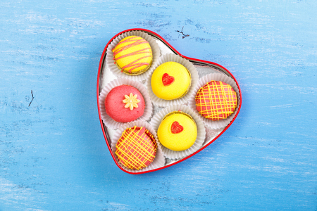 heartshaped: Macaroon cakes. Colorful almond macaron cookies. Love heart-shaped delivery box. Different flavors. On blue wooden rustic background. Stock Photo