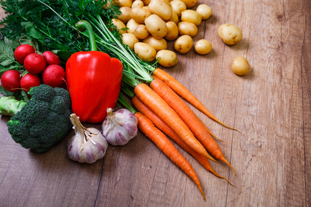 Potatoes with carrot, garlic and pepper. Red radish, brocoli and raw new potato. Fresh natural vegetables. Organic bio food. On wooden table. Stock Photo