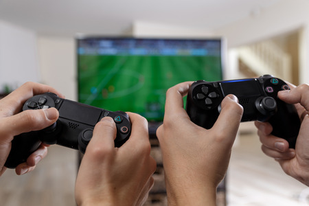 People playing video game. Hands holding console controller. Football or soccer game on the television. Widescreen tv stands on commode. Reklamní fotografie - 73823580