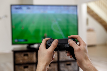 Man playing video game. Hands holding console controller. Football or soccer game on the television. Widescreen tv stands on commode. Stock Photo