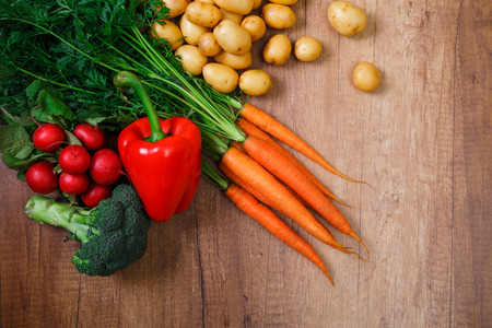 Potatoes with carrot and pepper. Red radish, brocoli and raw new potato. Fresh natural vegetables. Organic bio food. On wooden table. Stock Photo