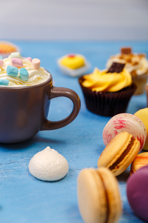 Cupcakes and macaroons cakes. Mug with whipped cream and marshmallows. Almond macaron cookies. Sweet dessert.