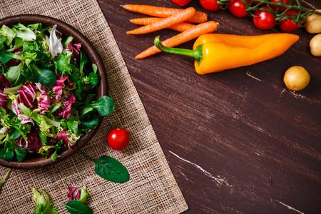 escarola: Ensalada de Provenza. Hojas de escarola o achicoria, cordero y ensalada de rosa. Tomates cherry, pimienta y zanahoria. Verduras crudas. En la mesa de madera.