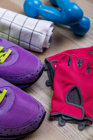 shoelace: Fitness gym equipment. Sneakers, dumbbells with towel. Workout gloves and footwear. Sport trainers with green shoelace.