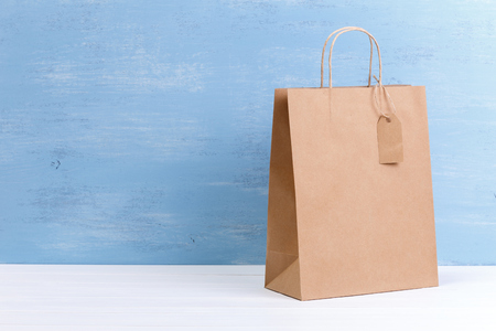 Mockup of blank shopping bag. Brown craft package. Concept for sales or discounts. Recycled paper. Blue wooden rustic board. Stock Photo