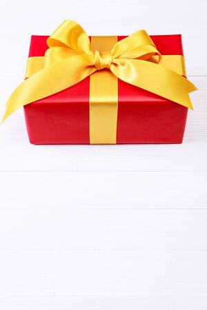 Gift box with yellow bow. Present wrapped with ribbon. Christmas or birthday red package. On white wooden table.