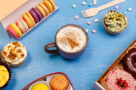 Cupcakes, macaroons and glazed donuts. Mug with whipped cream and cinnamon. Almond macaron cookies. Sweet dessert. Stock Photo