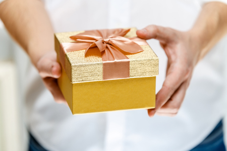 Male Hands Holding A Gift Box Present Wrapped With Ribbon And Bow Christmas Or