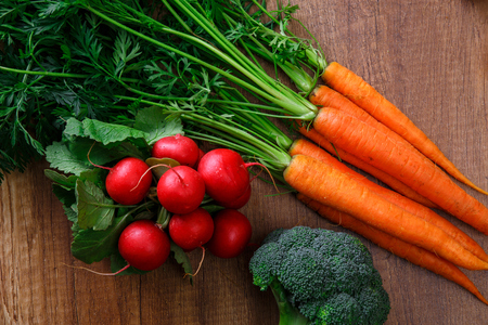 Carrot, red radish and brocoli. Fresh natural vegetables. Organic bio food on wooden table. Stock Photo