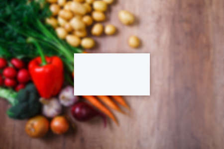 Business card mockup. Potatoes with carrot, garlic and pepper. Red radish, brocoli and raw new potato. Onion. Fresh natural vegetables.