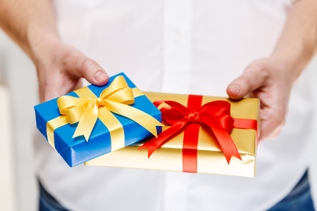 Male hands holding a gift boxes. Presents wrapped with ribbon and bow. Christmas or birthday blue, golden packages. Man in white shirt. Stock Photo
