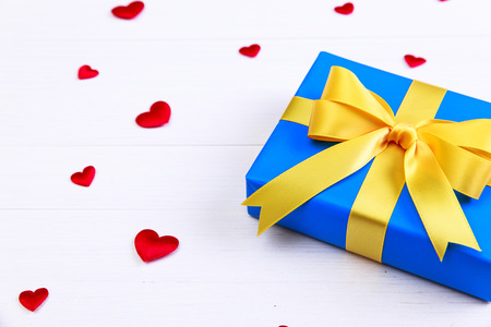 Gift box with red satin hearts. Present wrapped with yellow ribbon. Christmas or birthday blue package. On white wooden table. Stock Photo