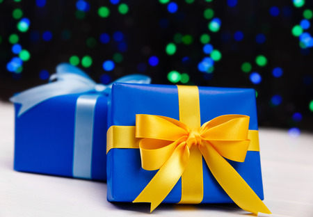 Gift boxes on blurred background. Presents wrapped with paper, bow and ribbons. Christmas or birthday packages. Celebration design. Stock Photo