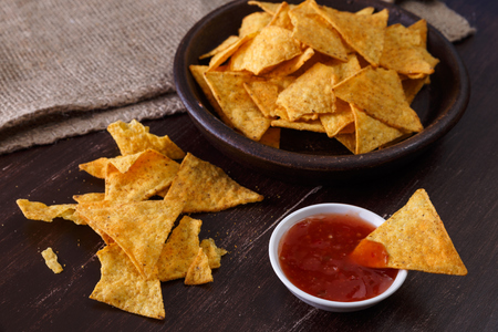 Nachos chips. Delicious salty tortilla with sweet salsa or chilli sauce on wooden background. Snack on rustic plate.