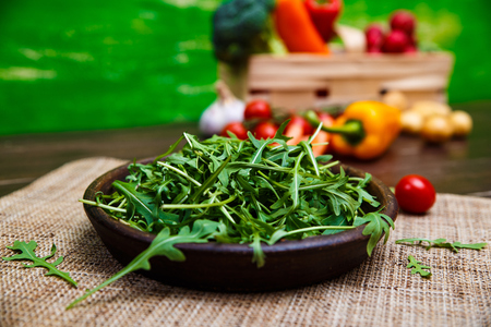 Arugula leaves in bowl. Fresh salad. Natural raw vegetables. Organic bio food on rustic wooden table. Imagens - 76056853