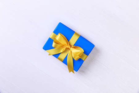 Gift box with yellow bow. Present wrapped with ribbon. Christmas or birthday blue package. On white wooden table.