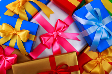 Gift boxes with bow. Colored presents wrapped with paper and ribbons. Christmas or birthday packages. Celebration design background. Stock Photo