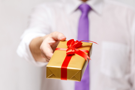 Male hand holding a gift box. Present wrapped with ribbon and bow. Christmas or birthday package. Man in white shirt and necktie. Stock Photo