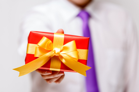 Male hand holding a gift box. Present wrapped with ribbon and bow. Christmas or birthday red package. Man in white shirt and necktie. Stock Photo