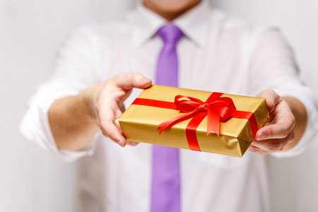 Male hands holding a gift box. Present wrapped with ribbon and bow. Christmas or birthday package. Man in white shirt and necktie. Stock Photo
