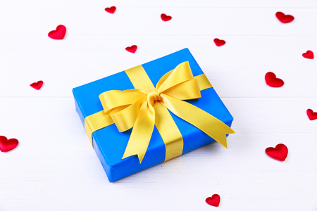 heartshaped: Gift box with red satin hearts. Present wrapped with yellow ribbon. Christmas or birthday blue package. On white wooden table. Stock Photo