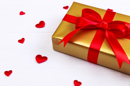 heartshaped: Gift box with red satin hearts. Present wrapped with ribbon and bow. Christmas or birthday golden paper package. On white wooden table.