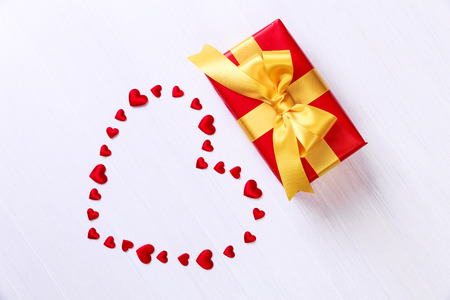 Gift box with red heart. Present wrapped with yellow ribbon. Christmas or birthday package. On white wooden table. Stock Photo