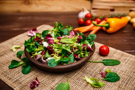 Provence salad. Leaves of endive or chicory, lamb and rose salad. Cherry tomato, pepper and carrot. Raw vegetables. On wooden table. Stock Photo