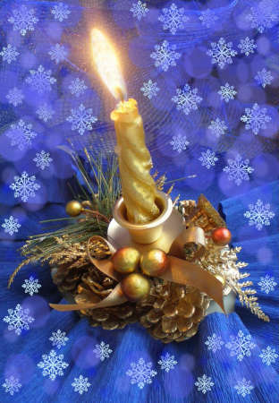 On a blue background with white snowflakes the decorative candle burns.The candle is surrounded with golden cones, berries with a tape and a green pine branch. photo