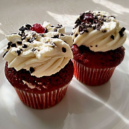 Red sponge cake muffin with cream filling. dessert decorated with fresh fruit cherries