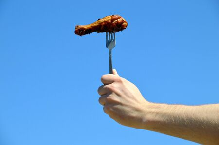 Hand holding fork with grilled appetizing chicken leg against the blue sky. Outdoor barbecue