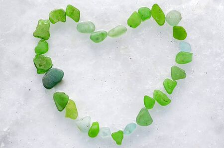 Heart made of green bottle glass on the ice of frozen Japanese sea. Glass beach, Russia.