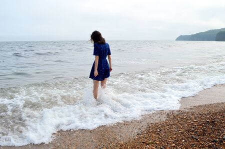 Upset thoughtful woman in blue dress going to the sea in cloudy weather before rain. She looking into the water