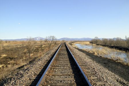 Railroad and depressive landscape with dry grass, swamp and blue sky