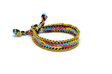 Selective focus of front side of the females woven friendship bracelet with ties. Handmade of multi-colored thread. Isolated on white background