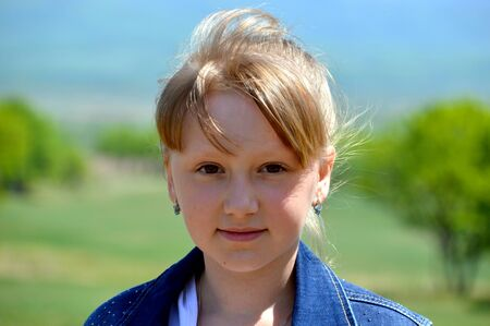 Portrait of 10 year old Russian smiling blonde girl on a background of green field. cute face, looking at the camera