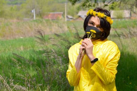 Brunette woman in yellow jacket with wreath of dandelions and medical black mask sniffing bouquet of dandelions. looking at camera.coronavirus pandemic concept.