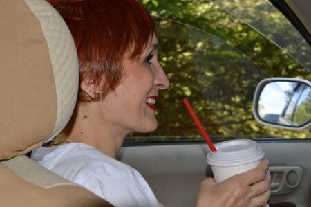 Cheerful young woman passenger with red hair sitting in the car, holding plastic cup of coffee and smiling with teeth. Summer adventures