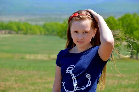 Portrait of 10 year old Russian blonde girl with long hair, hair band on a background of green field. cute face, looking at the camera
