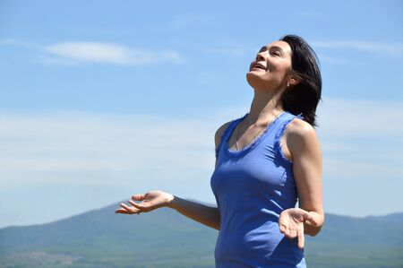 Young brunette woman with her head raised to the sky smiling with teath and enjoying freedom. sunny summer day