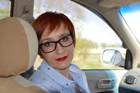 Business woman with glasses sitting on the seat of taxi car and looking at the camera. way to office
