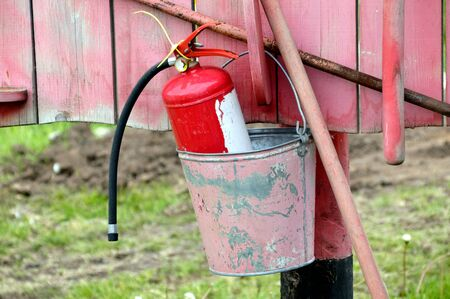 Fire extinguisher in a bucket hanging on a red board