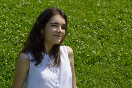 Portrait of young brunette woman winking and looking in the camera on a background of green meadow with clover