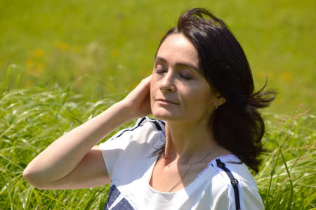 Portrait of 45 year old caucasian brunette woman with eyes closed on a green field. Enjoying the summer breath