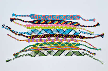 Multi-colored narrow woven friendship bracelets handmade of embroidery bright thread with knots isolated on white background