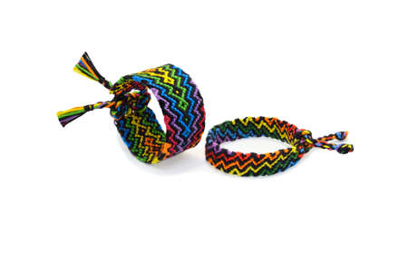 Selective focus of two multi-colored woven DIY friendship bracelets handmade of embroidery bright thread with knots isolated on white background