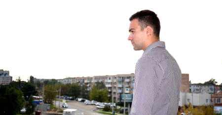 Man in office clothes standing on the balcony and looking at the old dirty Russian city of Bolshoy Kamen. He is sad and serious. depressive concept of loneliness, failure, loss of money