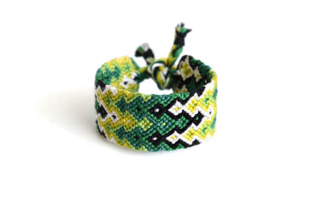 Selective focus of multi-colored woven DIY friendship bracelet handmade of embroidery bright thread with knots isolated on white background. Gradient pattern
