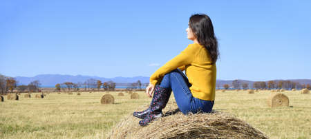 Young brunette woman in yellow sweater and rubber boots sitting on top of haystack in field. she looking at mountains, Japanese sea and the autumn forest. Primorsky kray, Russia. Beauty in nature.