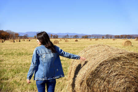Young brunette woman in denim jacket standing near haystack in field with bales of hay. she looking to the left. Primorsky kray, Russia. Beauty in nature. Copy space Stockfoto